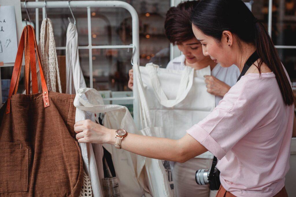 trendy young asian women choosing cotton bags in fashion boutique